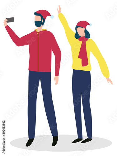 Man and woman making photo with smartphone. Male holding phone, doing selfie with female. Happy people wearing hat and scarf standing together. Couple celebrating winter holidays and shooting vector