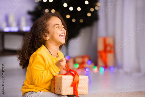 Obraz Excited african girl laughing with Christmas gift - fototapety do salonu