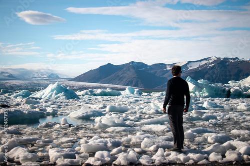 Fotografie, Obraz Guy standing on blocks of ice on black sand beach at Diamond Beach, Iceland in t