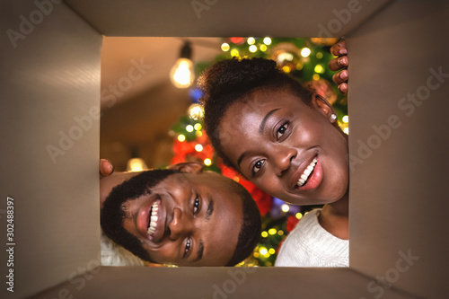 Fotobehang Dinosaurs Young african american couple opening Christmas present