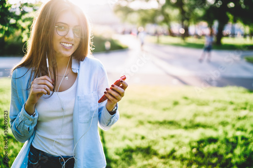 Fotografía  Portrait of smiling hipster girl in eyewear feeling carefree while resting in pa