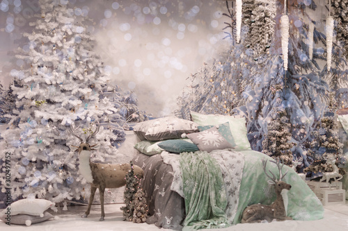 Fotografiet  Cozy bedroom interior decorated with Christmas details: soft deer toy, Christmas tree, branches at the wall near bed with snow