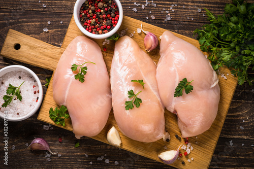 Photo Chicken fillet with ingredients for cooking on wooden table.
