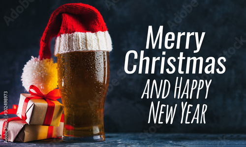 Glass beer mug in a Christmas Santa hat on a dark background . Merry Christmas and happy new year