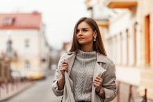 Pretty Cute Young Woman With Chic Brown Long Hair With Natural Make-up In Fashionable Trench Coat In Knitted Sweater Posing In A Spring Day Outdoors. Stylish Attractive Girl Model Resting In The City.