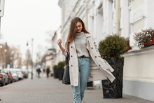 Stylish Model Of A Young Woman In Fashionable Seasonal Clothes With Bag Walks Around The City Near A Vintage Building On A Warm Autumn Day. Beautiful Girl In Trendy Outerwear Outdoors.