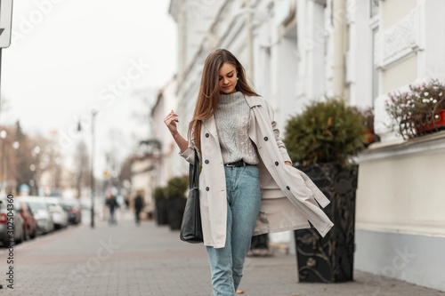 Stylish model of a young woman in fashionable seasonal clothes with bag walks around the city near a vintage building on a warm autumn day Fototapeta