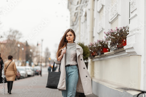 European young woman in fashionable outerwear with a leather vintage bag is walking on the street near a white building with flowers on the facade Slika na platnu