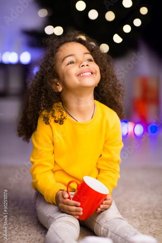 Little african girl enjoying warm cocoa near Christmas