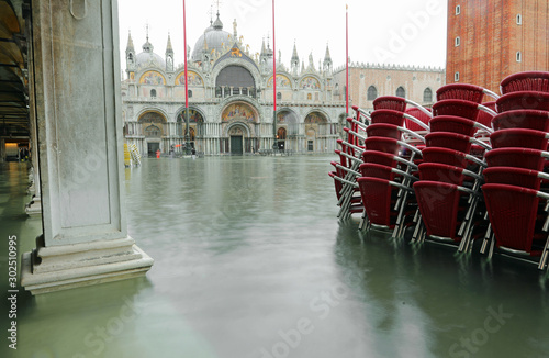 Red chairs in Saint Mark Square in Venice during awesome high ti Canvas Print