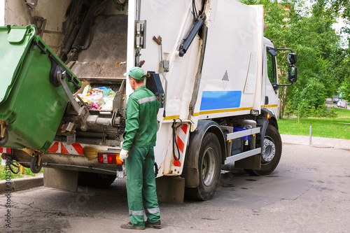 Obraz Garbage collection worker operating garbage compressor track in residential area. - fototapety do salonu