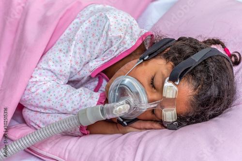 Child suffering from Sleep Apnea, wearing a respiratory mask. Wallpaper Mural