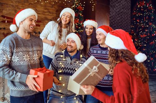 Obraz Happy friends with gifts celebrating Christmas - fototapety do salonu