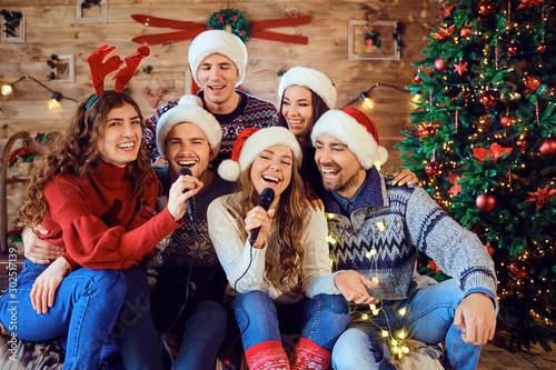 Laughing friends celebrating Christmas in karaoke - 302517139