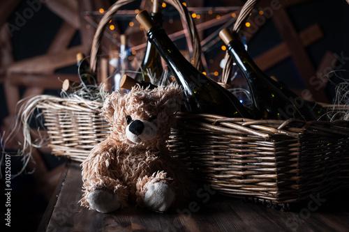 Fotografie, Obraz  Teddy bear, champagne bottle with Christmas basket, gold garlands on dark brown wooden background, new year celebration concept
