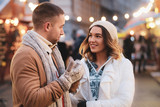 Beautiful romantic couple enjoy their Christmas day on traditional festive market.