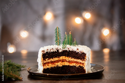 Christmas cake with cream on table with fairy lights Fototapet