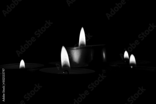 Mysterious grayscale  shot of candles lighting up creating a romantic atmosphere