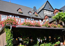 Traditional German Building Facade And Roof With Vineyard Covered Terrace And Geraniums In Germany