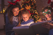 canvas print picture Parents reading fairytale to kids for Christmas Eve