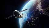Cargo spaceship on orbit of the Earth planet. Dark space. Elements of this image furnished by NASA