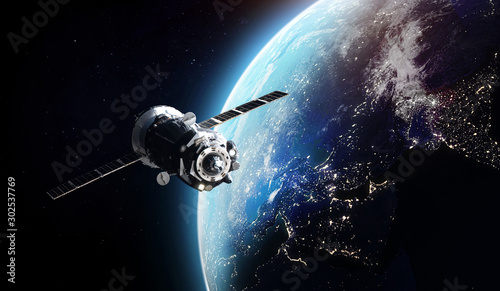 Cargo spaceship on orbit of the Earth planet. Dark space. Elements of this image furnished by NASA - 302537769