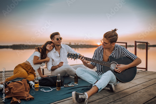 Happy friends playing the guitar and having fun on the beach - 302549363