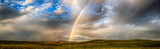Fototapeta Rainbow - Late rain storm showers across lush green landscape with rolling hills