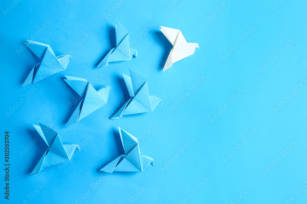 Fototapeta White origami bird among blue ones on color background. Concept of uniqueness