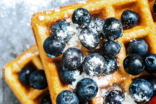 Close-up of waffles with tasty fruits cranberries, cherries and strawberries viewed from above, isolated on abstract background with copy space for text. - 302554335