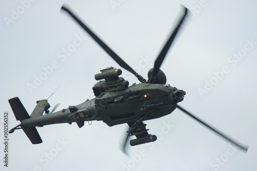 Apache helicopter turning blurred rotors underside view Canvas Print