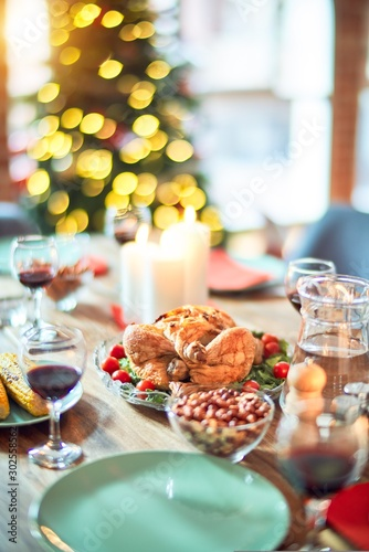 Setting of christmas table on festive holidays, full of traditional food with turky and delicious meals around the tree lights and decoration - 302558562