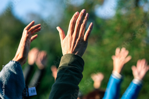 Fototapeta Selective focus photo of group of people standing outside while holding their ar