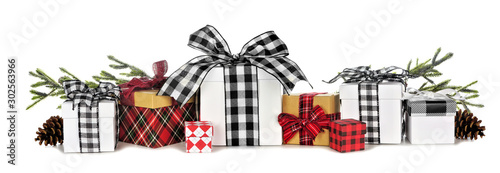 Assortment of many Christmas gift boxes with plaid wrap and ribbon and tree branches isolated on a white background - 302563966