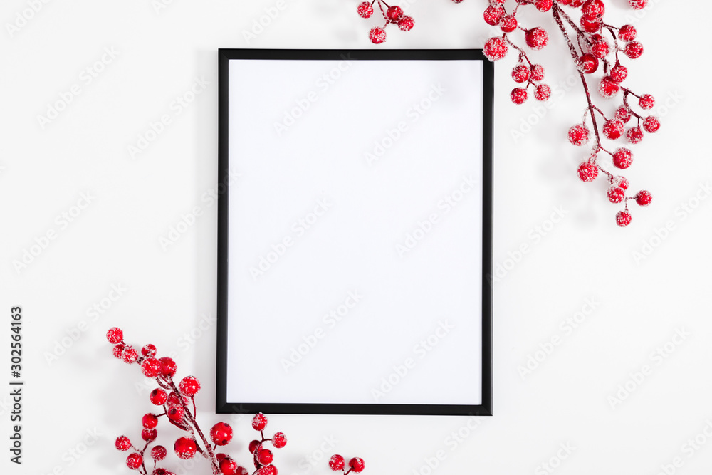 Fototapeta Christmas holiday composition. Black photo frame and red berry on white background. Christmas, New Year, winter concept. Flat lay, top view, copy space