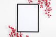 Christmas holiday composition. Black photo frame and red berry on white background. Christmas, New Year, winter concept. Flat lay, top view, copy space