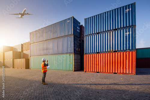 Valokuva Operator control at the port, loading containers for trucks for export and importing logistic background, control staff in Asia, loading containers for trucks for export and import