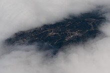 A Hill Top With Antennas Emerging From The Clouds