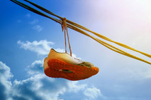 Sneakers Hang On A Wire Against A Blue Sky. The End Of A Sports Career.