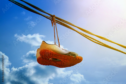 Fotomural  Sneakers hang on a wire against a blue sky
