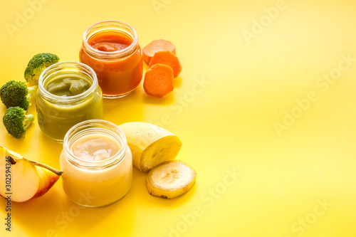 Photo sur Toile Magasin alimentation Baby food. Colorful puree in glass jars near vegetables and fruits on yellow background space for text