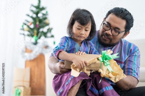 father and daughter sitting together and open the present in christmast day Fototapet