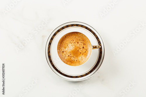 Tuinposter Cafe Cup of fresh americano or espresso coffee with golden foam froth on pile of brown raw coffee beans on white marble table background. Morning hot drink, coffee break, cope space