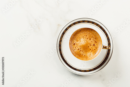 Tuinposter koffiebar Cup of fresh americano or espresso coffee with golden foam froth on pile of brown raw coffee beans on white marble table background. Morning hot drink, coffee break, cope space