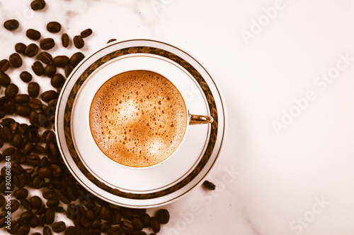 Wall Murals Cafe Cup of fresh americano or espresso coffee with golden foam froth on pile of brown raw coffee beans on white marble table background. Morning hot drink, coffee break, cope space