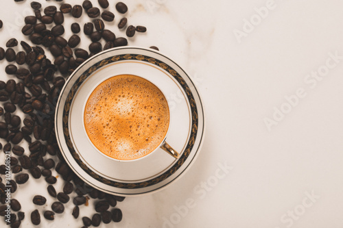 Foto op Aluminium Cafe Cup of fresh americano or espresso coffee with golden foam froth on pile of brown raw coffee beans on white marble table background. Morning hot drink, coffee break, cope space