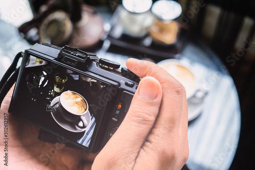 Fototapeta  Photography blogging workshop concept. Hand holding camera takin