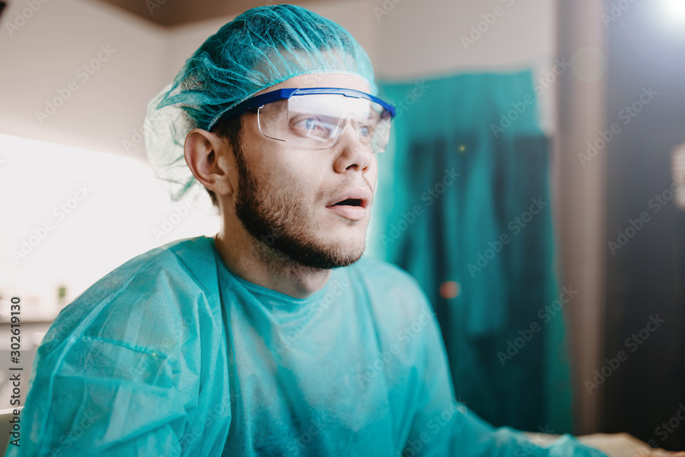 Fototapeta surgeon in uniform is working with a computer in a medical office, training doctors.