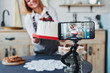 Woman makes delicious sweets and pie. Recording process by smartphone on tripod
