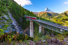 Zermatt, Switzerland. Gornergrat Red Tourist Train On The Bridge And Matterhorn Peal Panorama In Swiss Alps